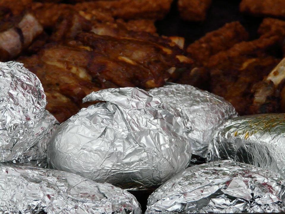 焼きたてのジャガイモ ジャガイモ料理 アルミ箔 箔のジャガイモ ポテトをグリルします バーベキュー