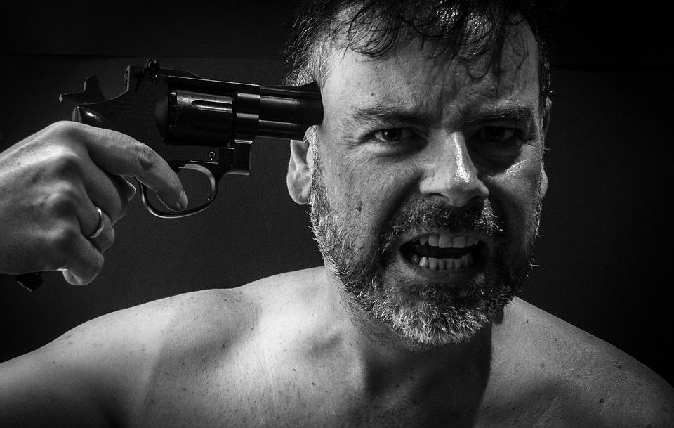 銃口を頭につけている男性