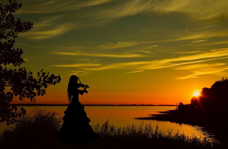 日没にヴァイオリンを弾く女性