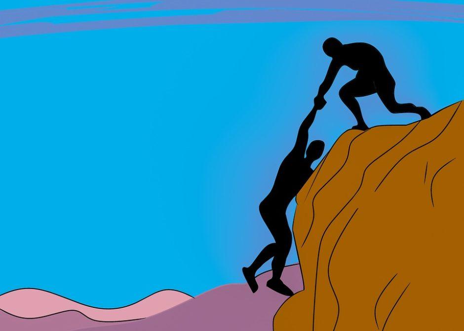 崖から落ちそうな友達を助けようとする人